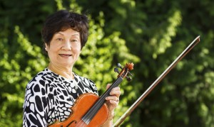 Senior Woman Relaxing from playing the violin outdoors